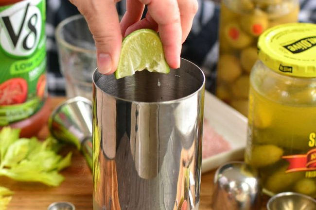close up of mixing tin as a lime gets squeezed into tin. Bottles of pickles, olives and V8 brand juice surround the tin with a jigger and glass in the background.
