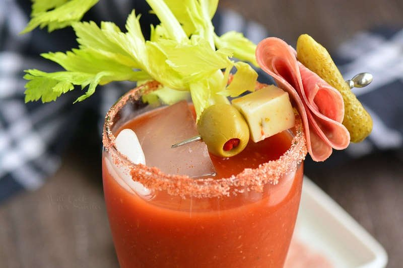 Top of glass shown filled with bloody mary and topped with a speared olive, pickle, cheese and meat garnish as a celery stalk rests on the rim of the glass. A wooden table below with a black and white cloth in the background.