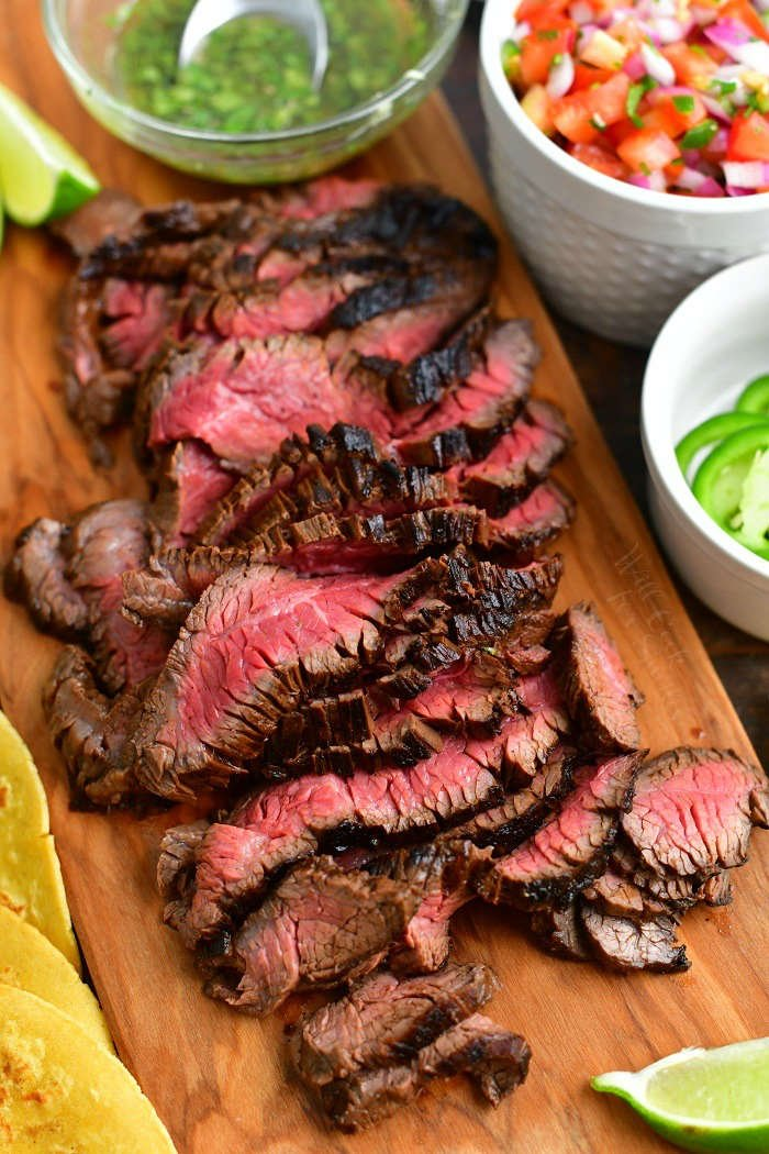 sliced grilled steak on a cutting board with taco toppings visible around