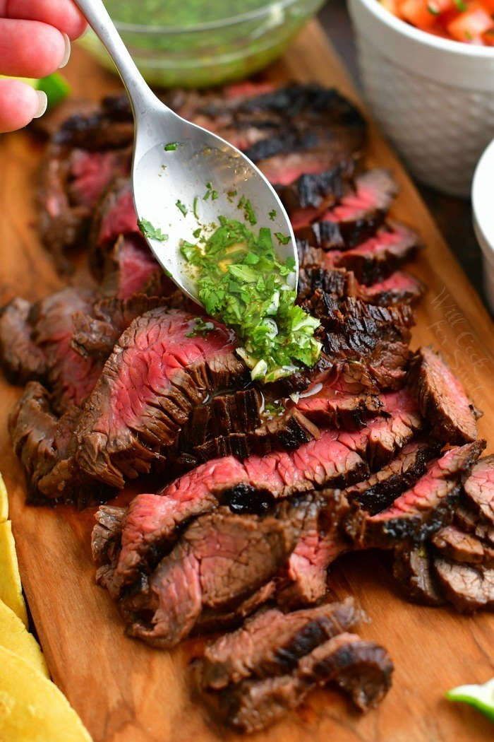 spooning cilantro lime topping over the sliced steak on the cutting board