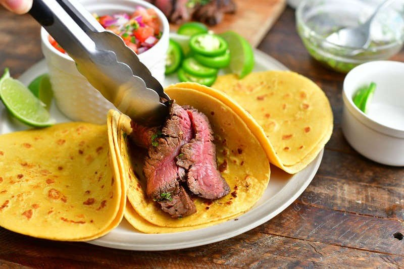 placing sliced steak into taco shells using metal tongs with pico, jalapeno slices, and lime wedges around