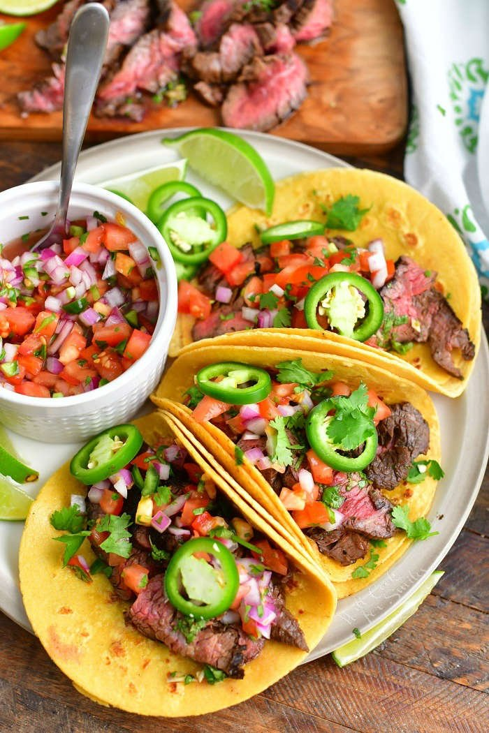 three steak tacos on a plate side by side with a bowl of pico in a plate and sliced steak on a cutting board next to the plate