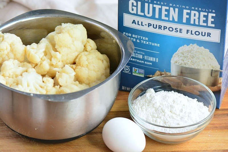 ingredients standing on the cutting board: cooked cauliflower in a metal bowl, small glass bowl of gluten free flour, box of gluten free flour, and 1 egg