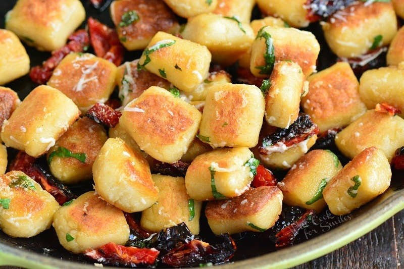 crispy cauliflower gnocchi in a pan with sundried tomatoes, basil and Parmesan