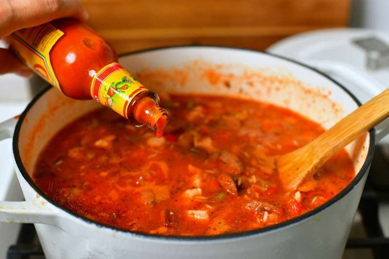 adding a few drops of hot sauce into the pot of jambalaya while it's cooking on the stove