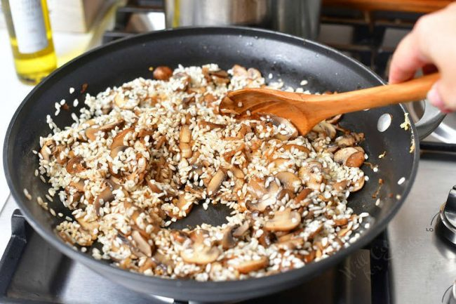 woman's hand stirring risotto rice with wooden spoon