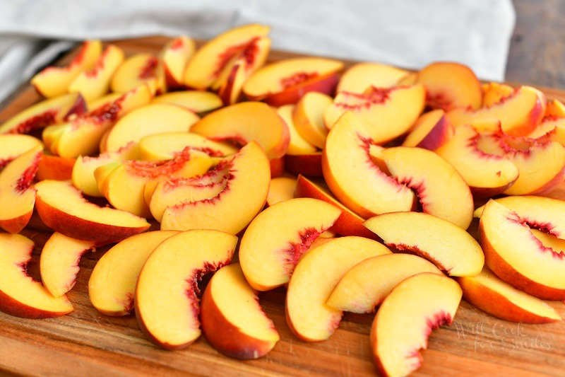many slices of peaches spread out on the wooden cutting board