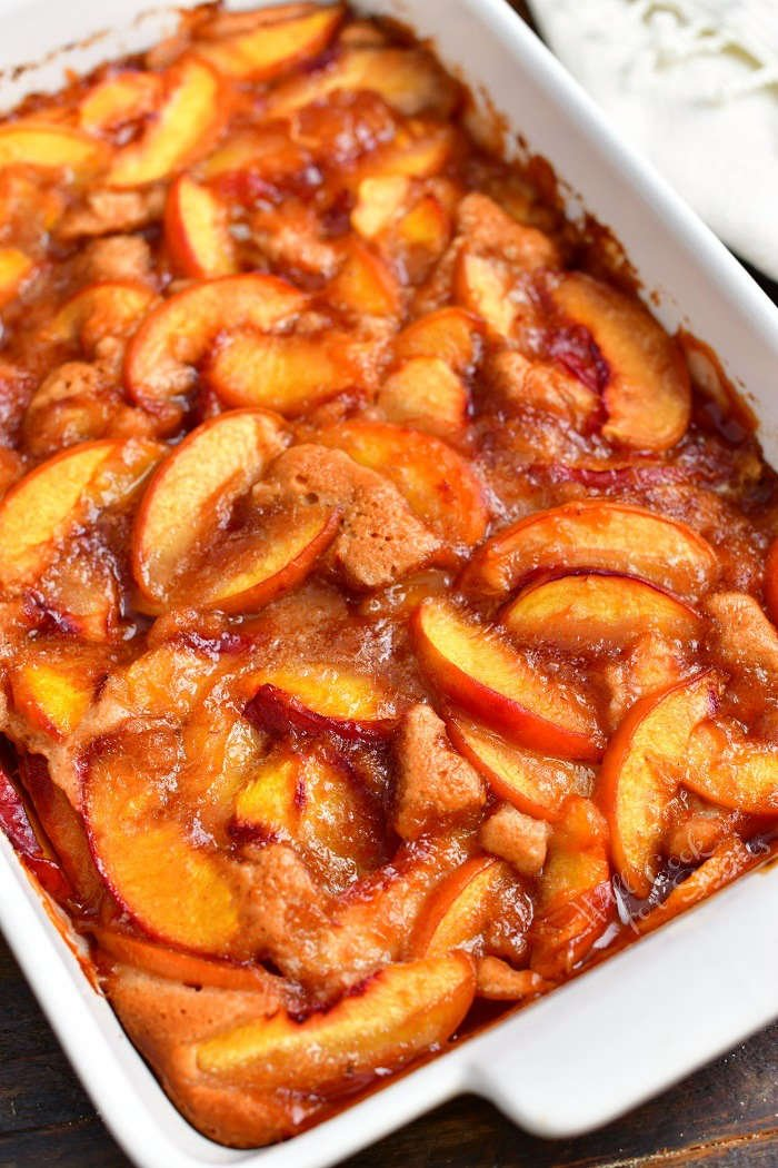 closer view of cooked peach cobbler in a white baking dish