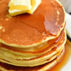 top view of the stack of pancakes topped with 2 slices of butter and maple syrup