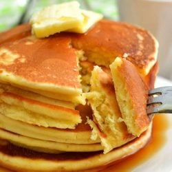 pulling off two pieces of pancake cut off the stack of pancakes with a fork
