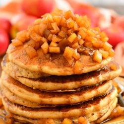 closeup view of 6 stacked pancakes topped with apple pie topping