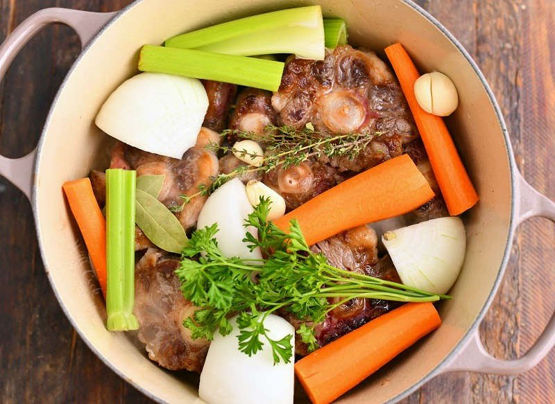 beef bones, chopped vegetables, and fresh herbs in large pot for stock