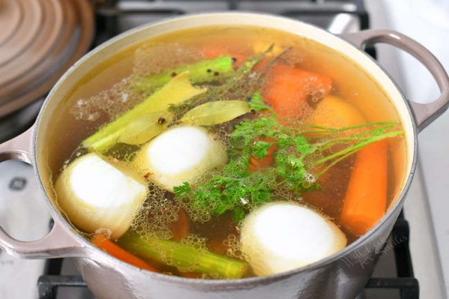 pot with vegetables and other ingredients to make homemade stock in large white pot