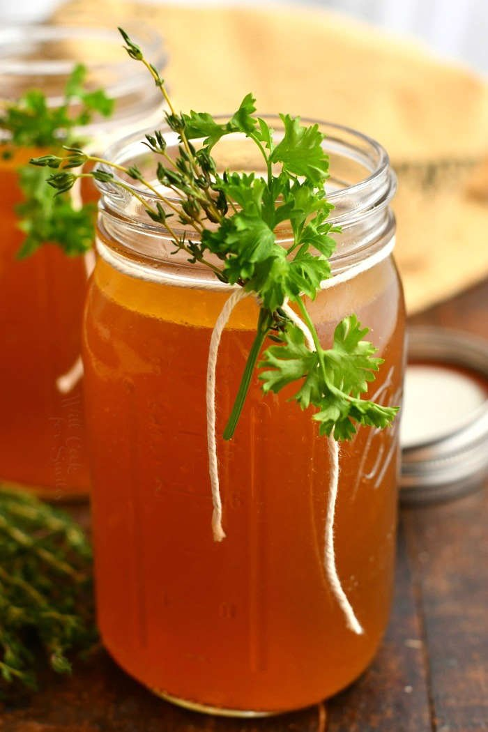 homemade stock in glass canning jar garnished with fresh herbs
