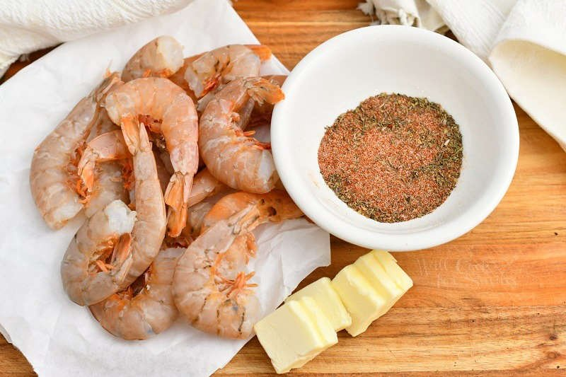 raw shellfish on paper towel, pats of butter and bowl of ground spices all on a wood cutting board