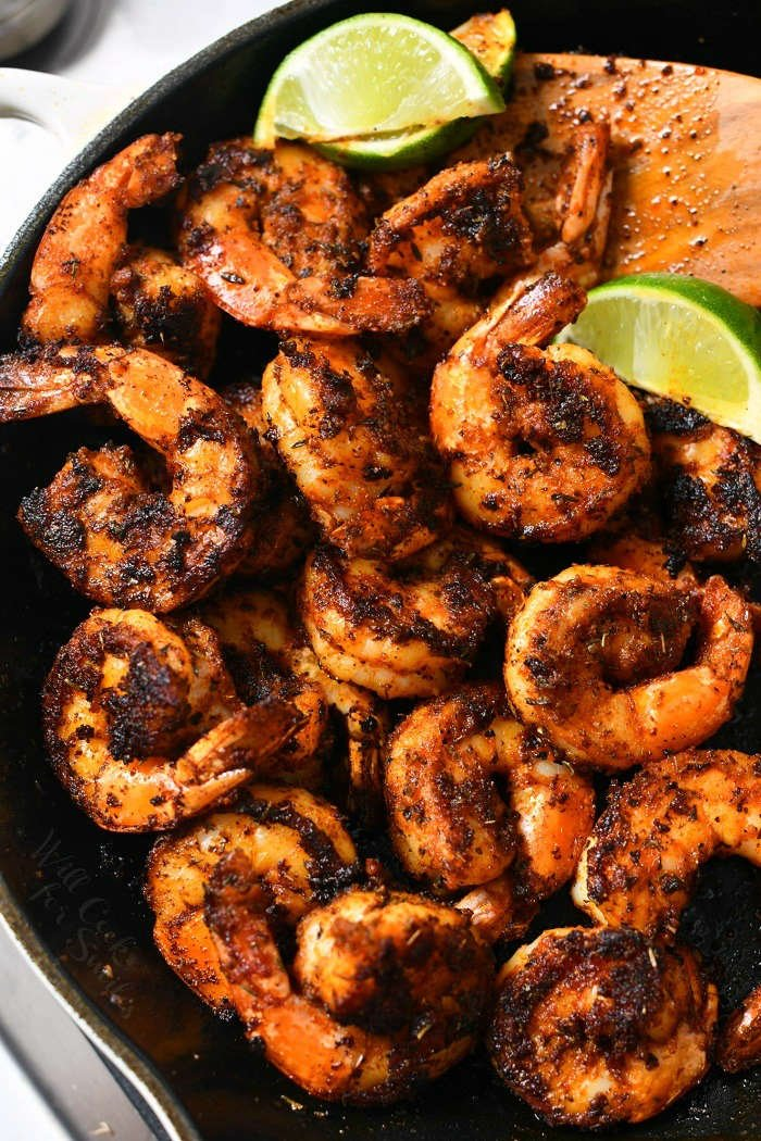 overhead photo: spicy tail-on shrimp in black cast iron pan with lime wedges