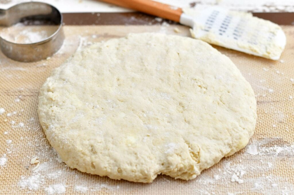 unbaked circle of dough on floured pastry mat