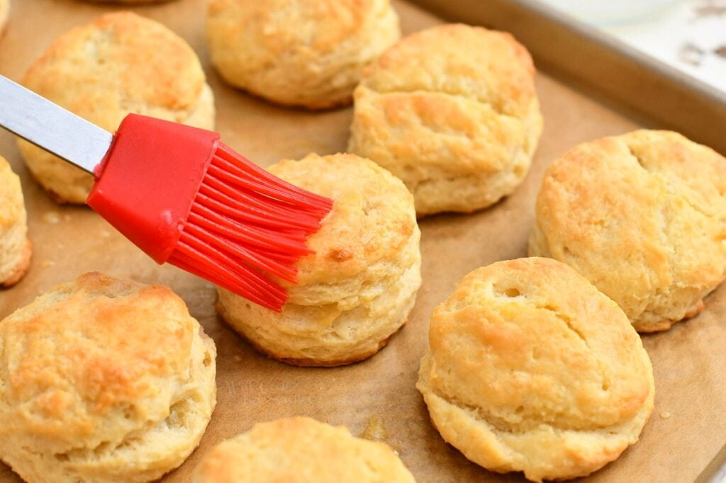 brushing tops of homemade biscuits with melted butter