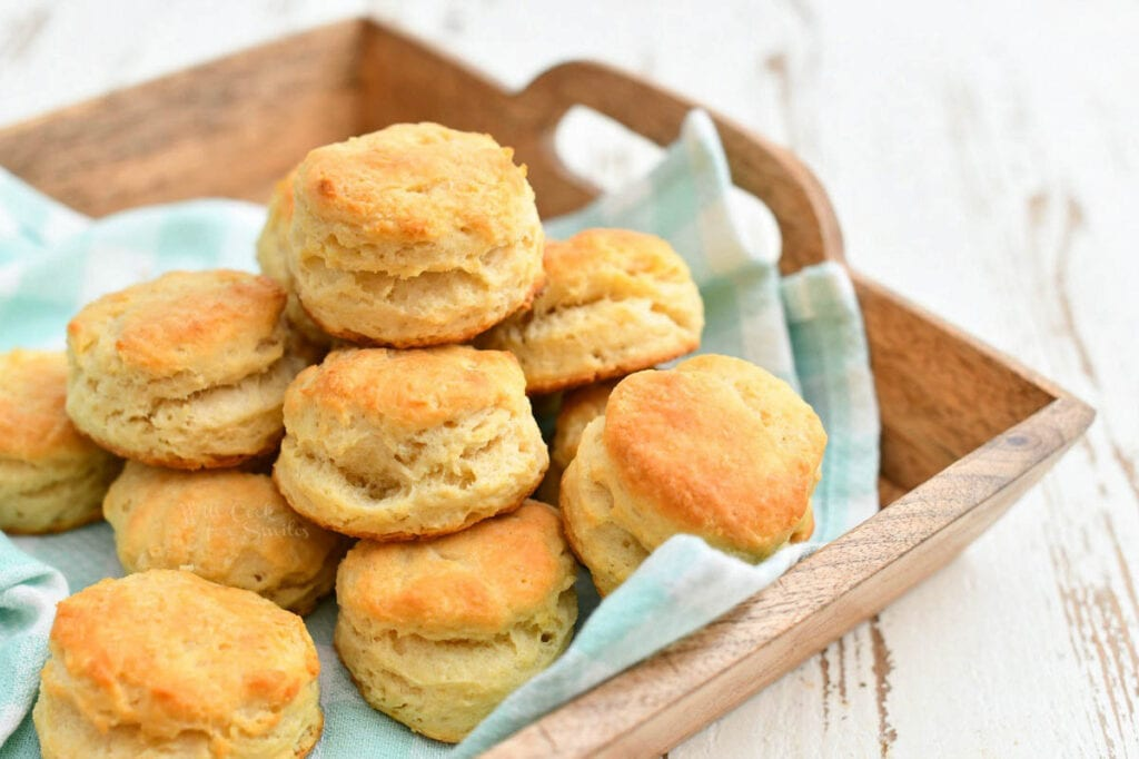 homemade country biscuits on green cloth napkin in wood serving tray
