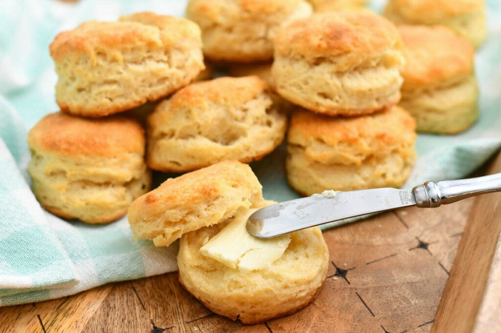 knife schmearing butter onto a warm biscuit - stack of them behind it