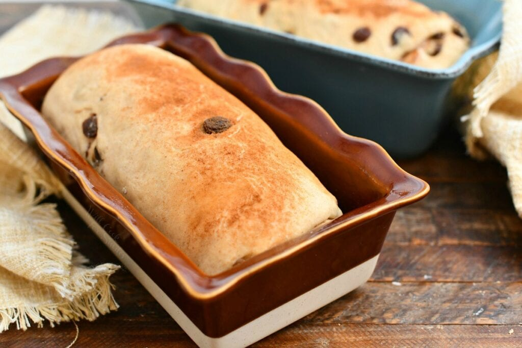 homemade loaf of yeast bread in red glazed stoneware loaf pan