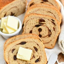 slices of freshly baked cinnamon swirl bread next to tabs of butter in white dish