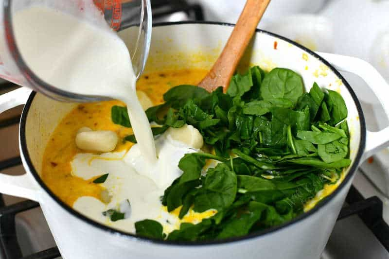 pouring heavy cream into white Dutch oven with fresh spinach