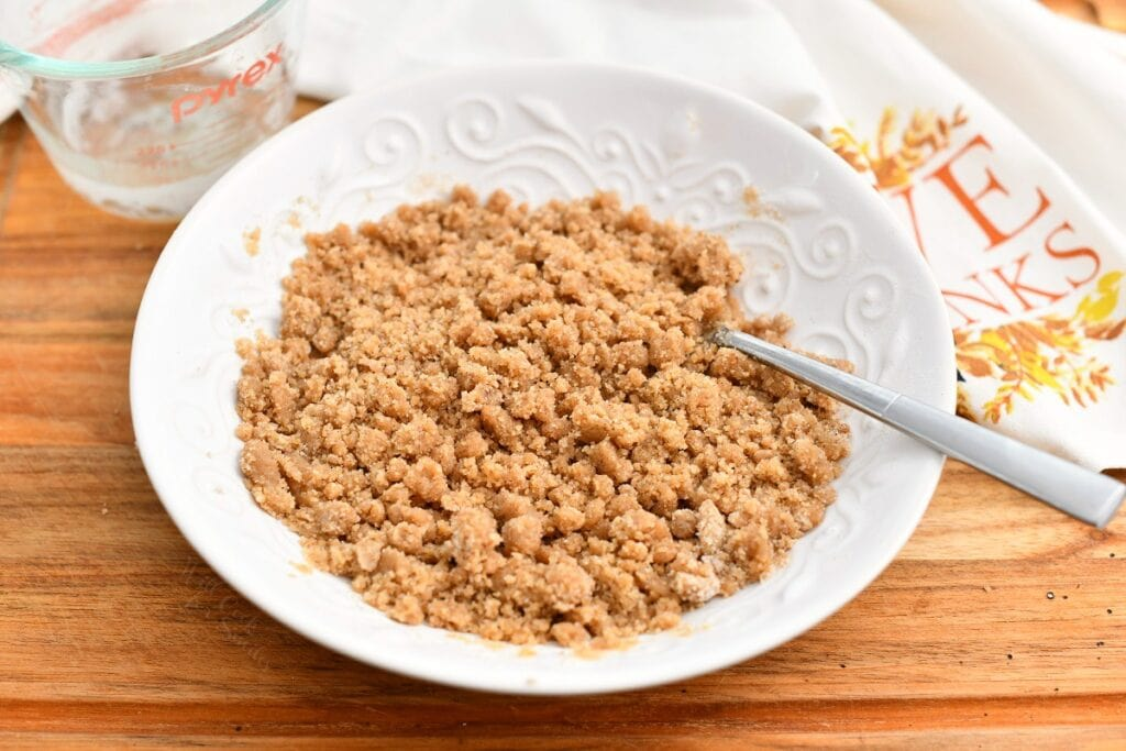 brown sugar crumble topping in white bowl with spoon