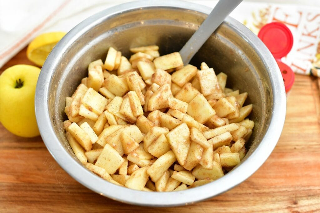 stirring fresh apple slices in a bowl with cinnamon sugar mixture
