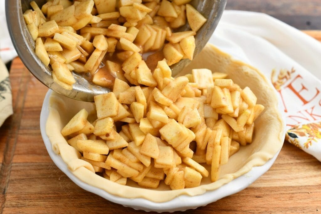 pouring spiced apple mixture into unbaked pie crust