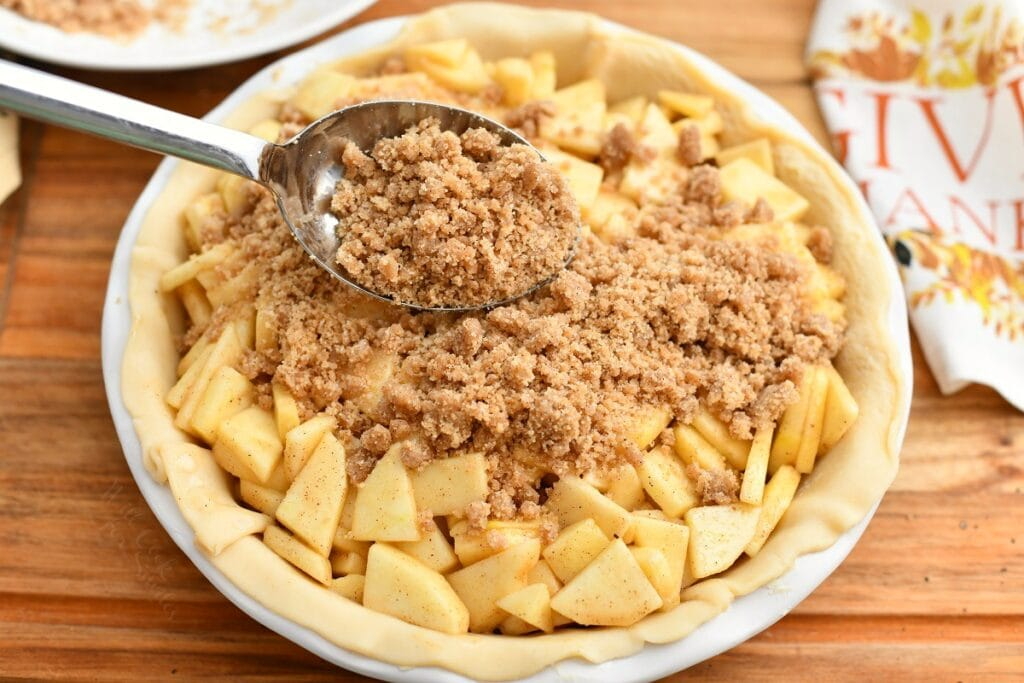 using spoon to add streusel topping for apple pie