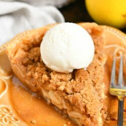 slice of Dutch apple pie with scoop of vanilla ice cream on brown plate