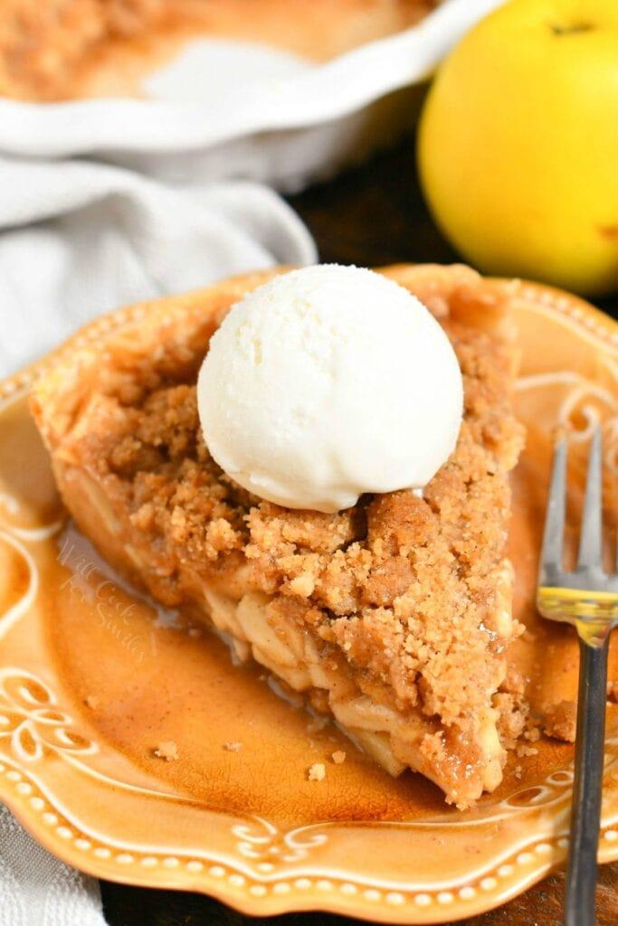 slice of Dutch apple pie with scoop of vanilla ice cream on brown plate