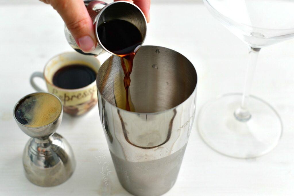 pouring the coffee liqueur into the cocktail shaker