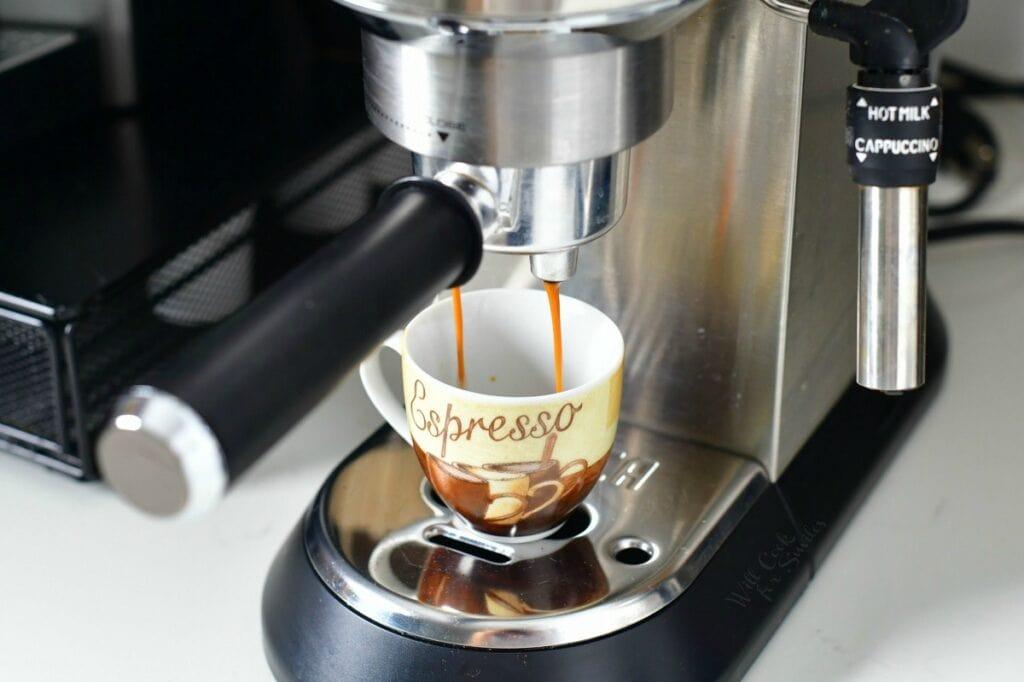 espresso maker pouring espresso into small mug