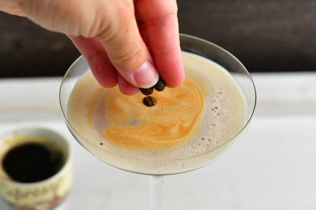 garnishing the cocktail with coffee beans