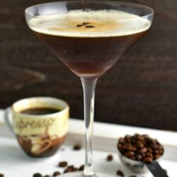side view of tall martini glass with the cocktail and coffee beans and espresso shot next to it
