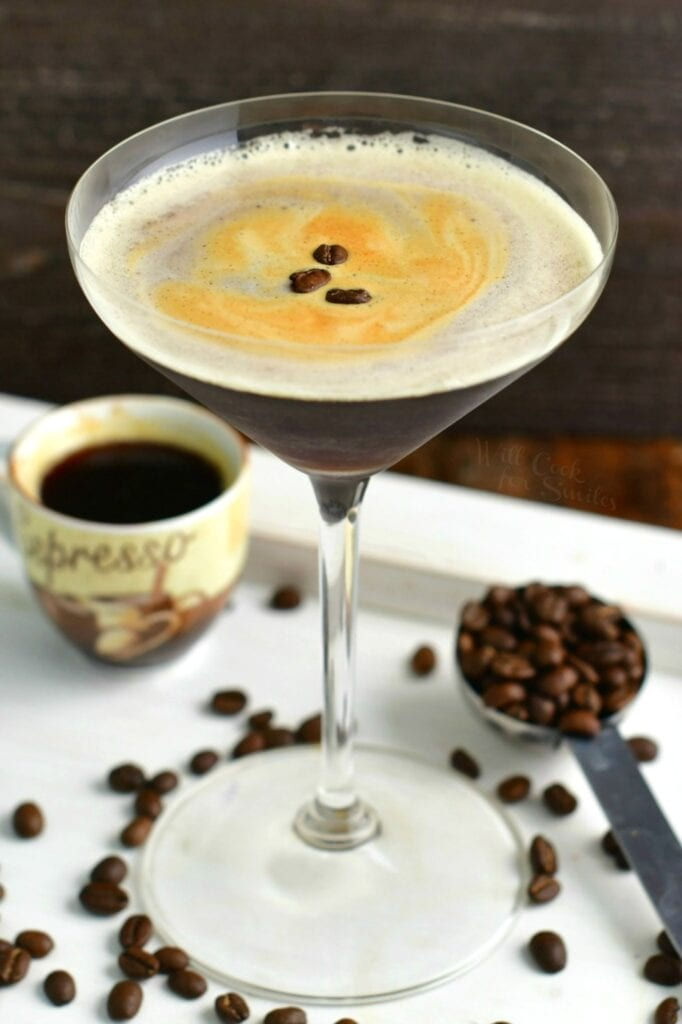 top view of espresso martini in a tall glass with beans and espresso shot around