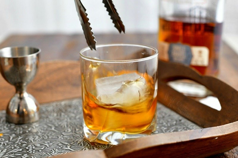 side view: metal tongs dropping ice cube into whiskey cocktail