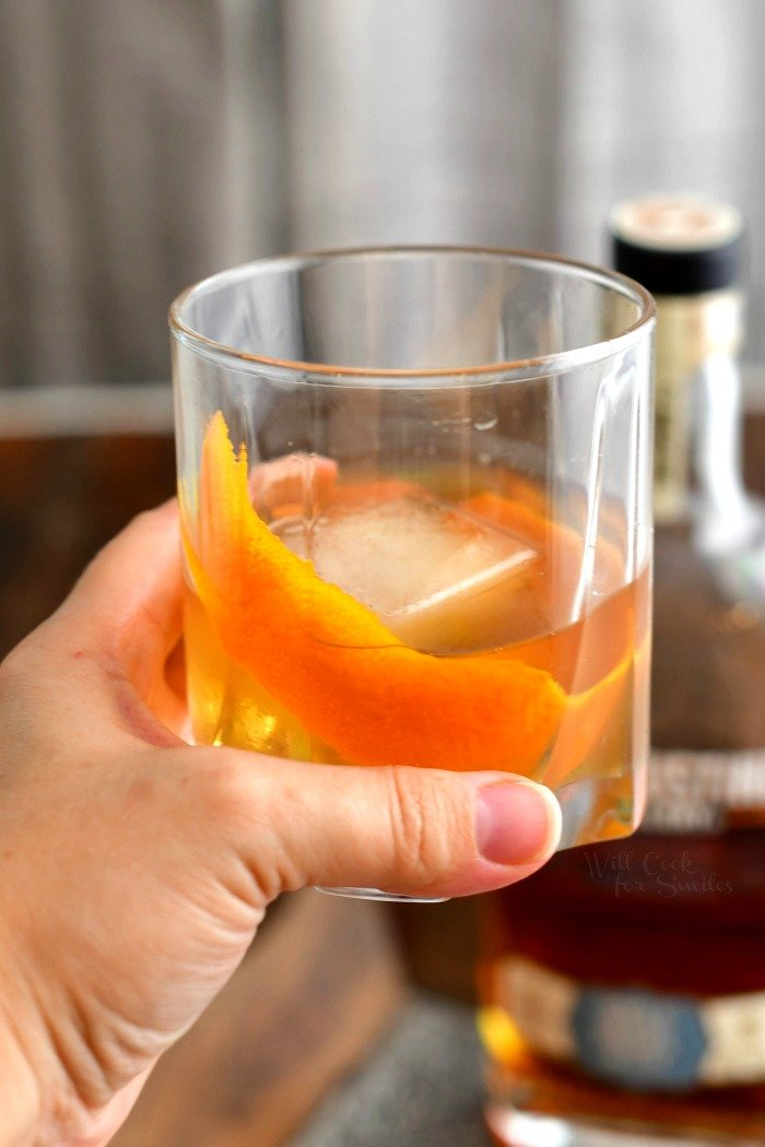 woman's hand holding cocktail over ice in low ball glass with orange peel
