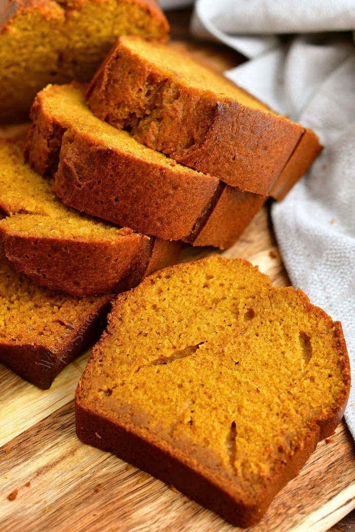 thick slices of moist pumpkin bread on wooden serving board with white linen napkin