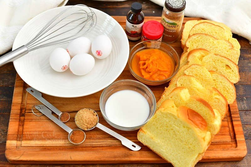 sliced bread, eggs, pumpkin, milk, and spices laid out on the cutting board