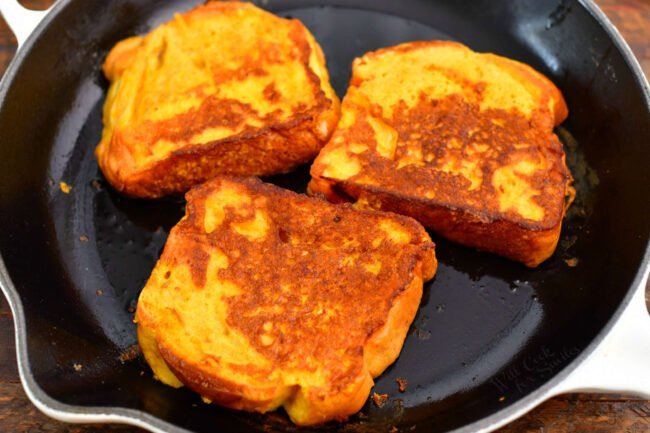three slices of pumpkin French toast cooking in a skillet