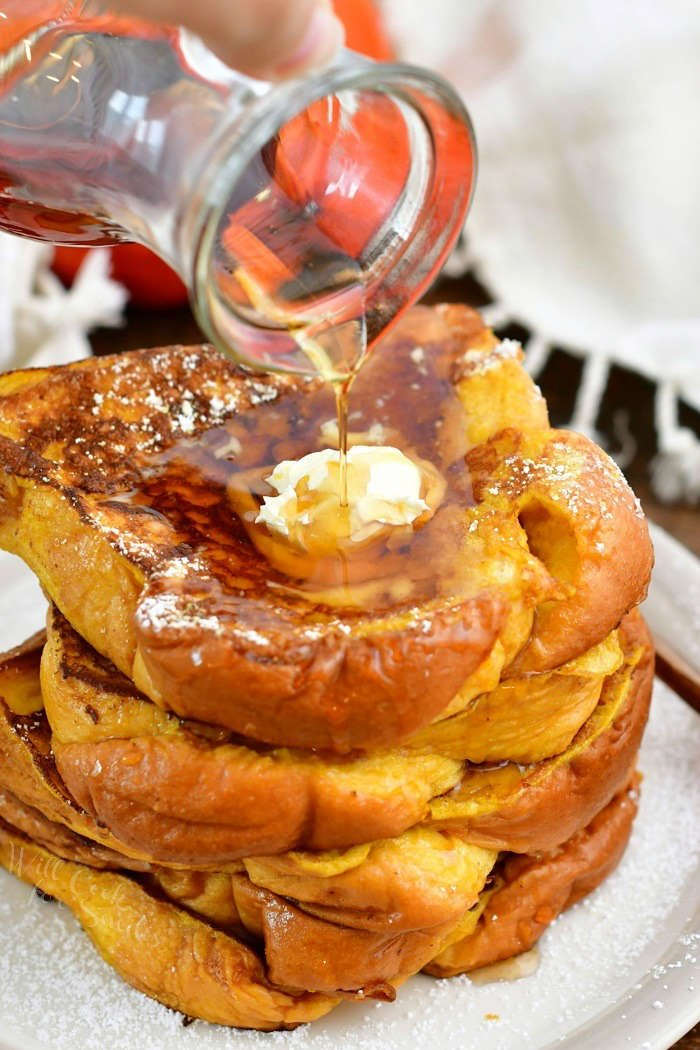 pouring syrup onto the stack of French Toast out of a glass jar