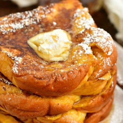 closeup top view of stack of French Toast topped with butter, syrup, and powdered sugar