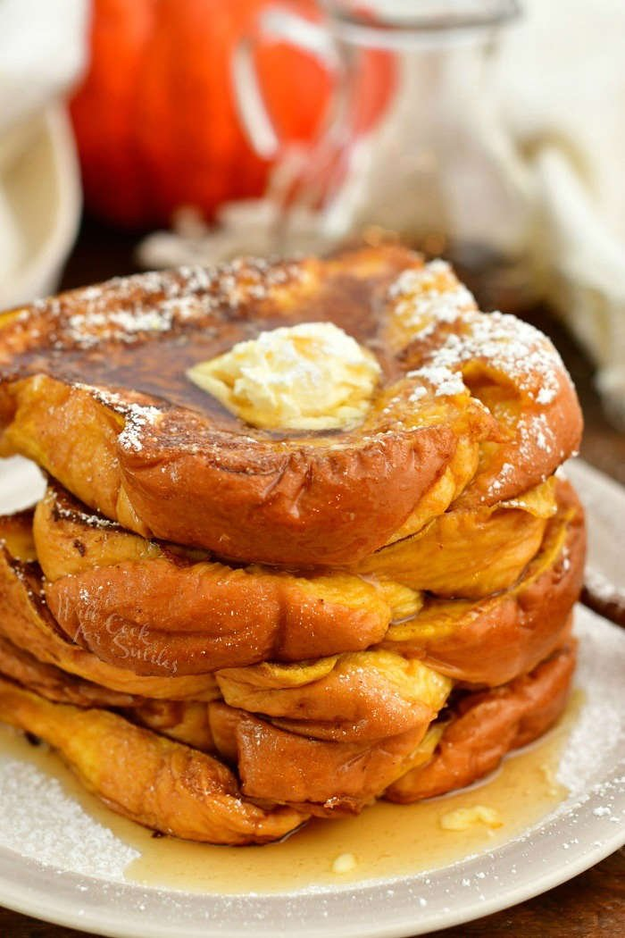 stack of Pumpkin French toast on a plate topped with scoop of butter, syrup, and powdered sugar