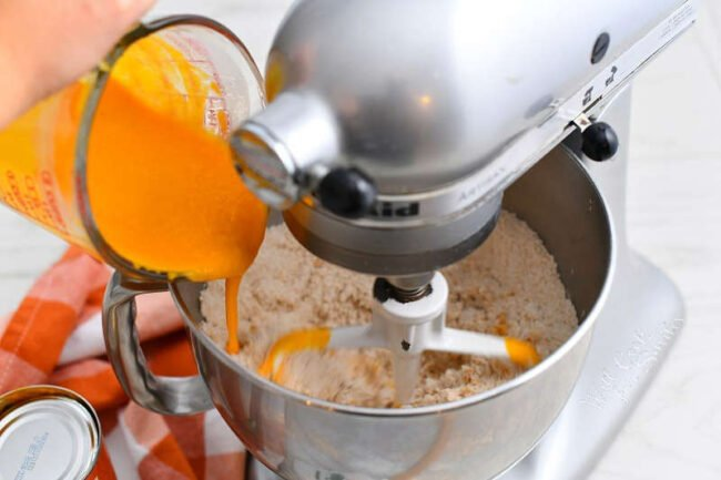 adding pumpkin puree mixture to bowl of a stand mixer with flour in it