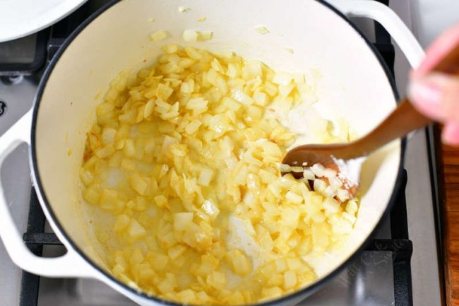 photo shows how to make tomato soup by sauteeing onions in large white pot on stove top