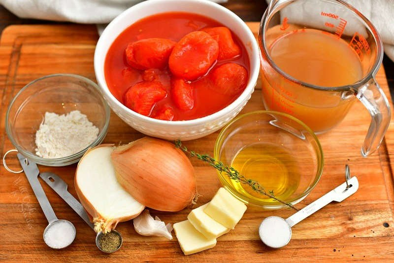 ingredients in measuring cups, spoons, and bowls to make homemade tomato soup