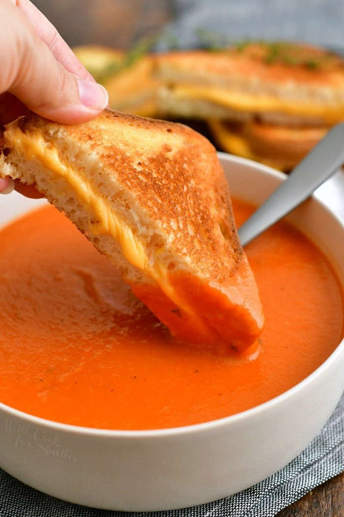 dipping grilled cheese sandwich into bowl of creamy tomato soup
